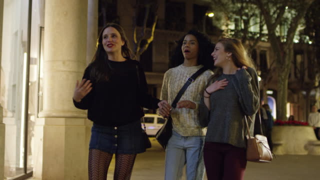 happy women talking while walking in city at night - window display stock videos and b-roll footage