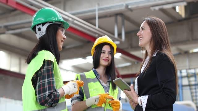 glückliche frauen arbeiten und reden gemeinsam in der fabrik - fließbandarbeiter stock-videos und b-roll-filmmaterial