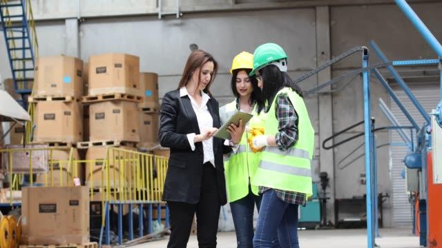 幸せな女性が働いて、工場で一緒に話す - 説明する点の映像素材/bロール
