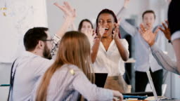 Happy young African American female boss celebrating success with multiethnic team, confetti falling at office meeting.