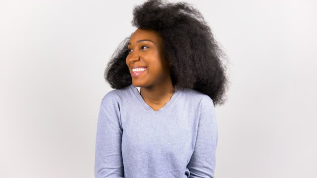 Happy young afro woman in purple sweater