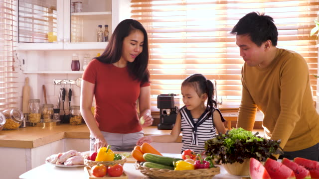 happy young asian family preparing and cooking healthy food in kitchen, family relaxing and spending time together at home - meal preparation stock videos & royalty-free footage