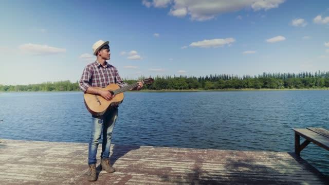 vidéos et rushes de heureux jeune homme asiatique jouer de la guitare classique et se tenait à lakeside et bleu ciel à l'arrière-plan, espace copie - guitariste