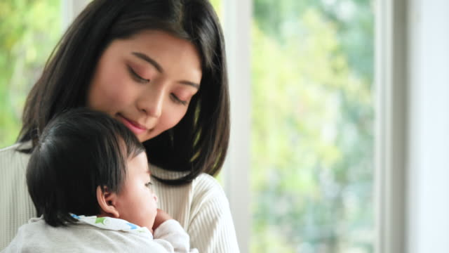 vídeos y material grabado en eventos de stock de feliz joven mujer asiática abrazando a su bebé. - miembro humano