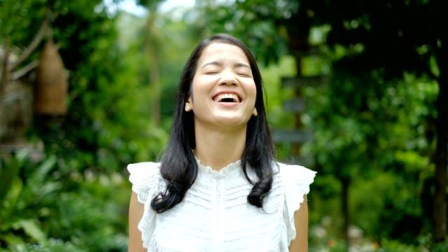 Glückliche junge Asiatin im weißen Anzug Lächeln und Lachen vor grünen Natur Hintergrund