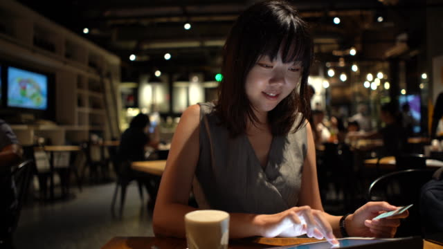 happy young asian woman online shopping using credit card and digital tablet in cafe - online shopping stock videos & royalty-free footage