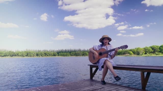 vídeos de stock, filmes e b-roll de mulher asiática nova feliz que joga a guitarra clássica na beira do lago e no céu azul no fundo, espaço da cópia - violão acústico