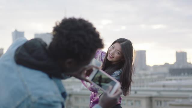 Glückliche junge Asiatin posiert auf Dach, Fotograf mit smartphone