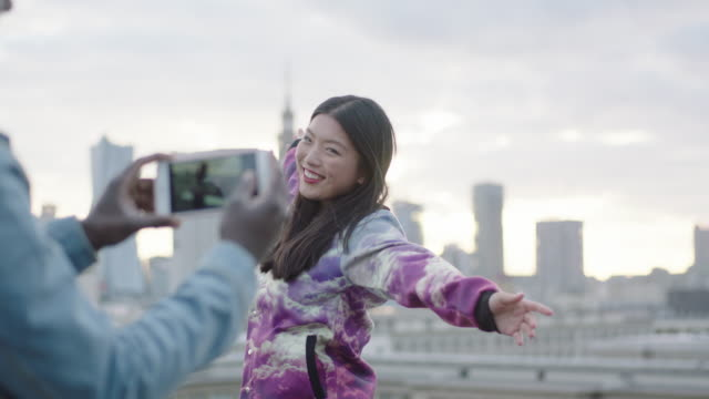 happy young asian woman posing on roof to photographer with smartphone - music video stock videos and b-roll footage