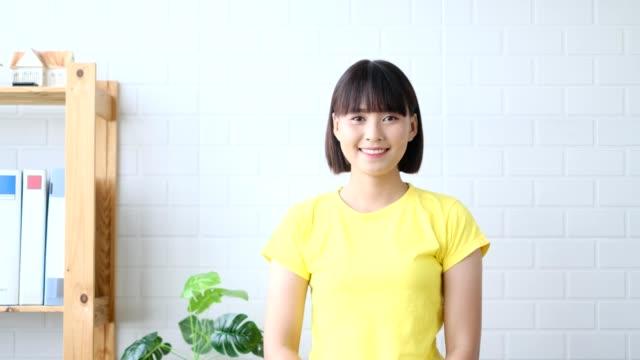 glad ung asiatisk kvinna leende korsar armar och står över vit vägg bakgrund. söker kamera, hon är mycket upphetsad - endast unga kvinnor bildbanksvideor och videomaterial från bakom kulisserna