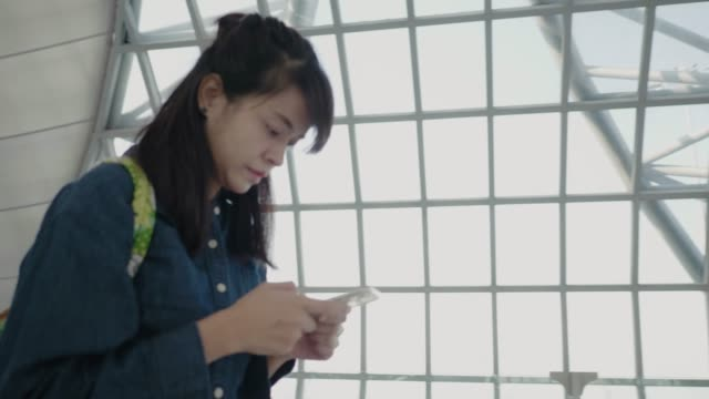 Happy young asian woman using Smart phone at airport