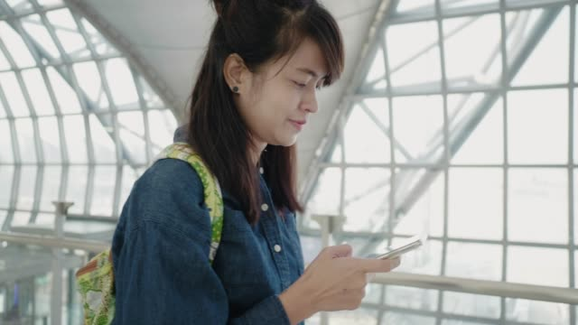 happy young asian woman using smart phone at airport - transportation building type of building stock videos & royalty-free footage
