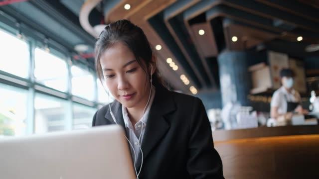 vídeos y material grabado en eventos de stock de feliz joven asiática trabajando en el café. - coreano oriental
