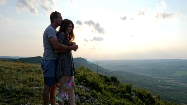 vídeos de stock, filmes e b-roll de um jovem lindo casal feliz se divertindo na natureza ao pôr do sol, no amor, romance, companheirismo, desfrutando a passar tempo juntos, são valentim, felicidade, - olhando para vista
