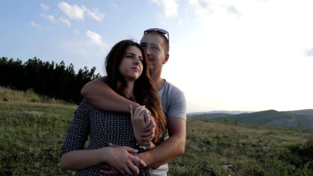 vidéos et rushes de un jeune beau couple heureux s'amuser dans la nature au coucher du soleil, dans l'amour, de romance, de convivialité, de profiter de passer du temps ensemble, saint-valentin, bonheur, - coup de foudre