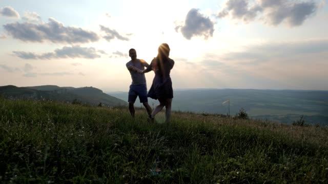vídeos de stock, filmes e b-roll de um jovem lindo casal feliz se divertindo na natureza ao pôr do sol, no amor, romance, companheirismo, desfrutando a passar tempo juntos, são valentim, felicidade, - casal jovem