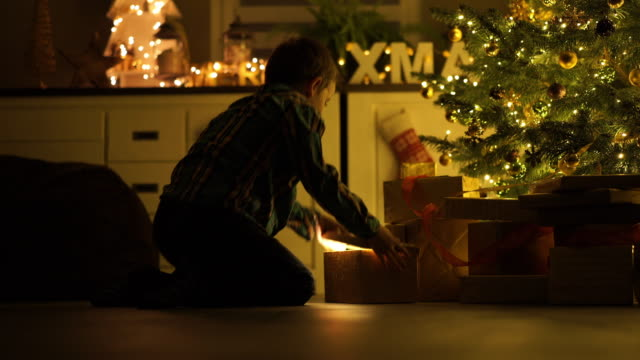 happy young brothers with presents at christmas tree