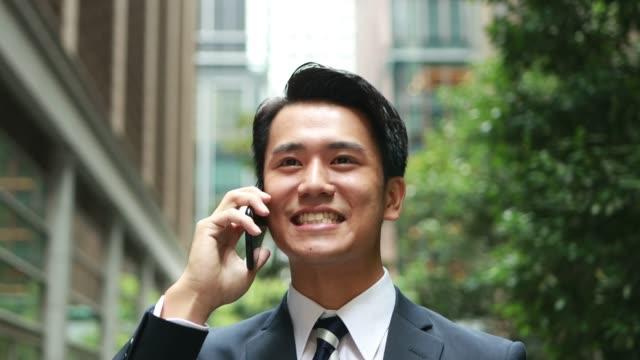 アジアで電話で話す幸せな若いビジネスマン - 電話を使う点の映像素材/bロール