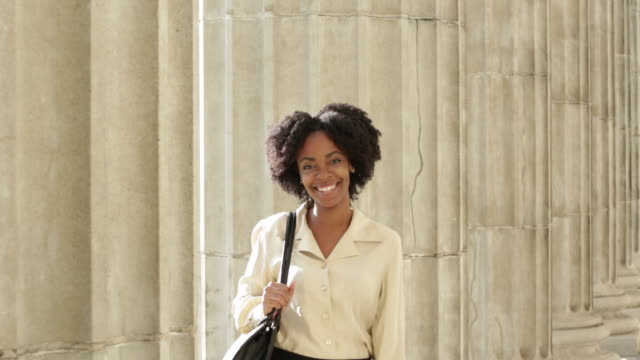 CU Happy young businesswoman walks into shot between pillars of building and stands smiling into camera.