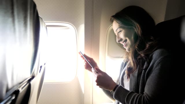 happy young caucasian woman uses smartphone on airplane - abitacolo video stock e b–roll