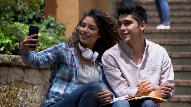 vídeos y material grabado en eventos de stock de pareja joven feliz en el campus de la universidad tomando un selfie diversión - person in further education