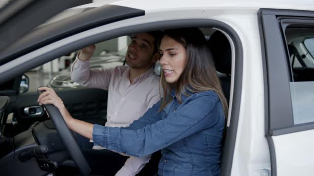 vidéos et rushes de jeune couples heureux vérifiant l'intérieur d'une voiture tout en parlant et souriant - essai de voiture