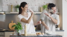 Happy Young Couple Cooks in the Kitchet. As a Joke They Started Throwing Flour at Each Other. Then Smilingly Embrace.