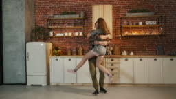 Happy Young Couple Dances In The Kitchen.