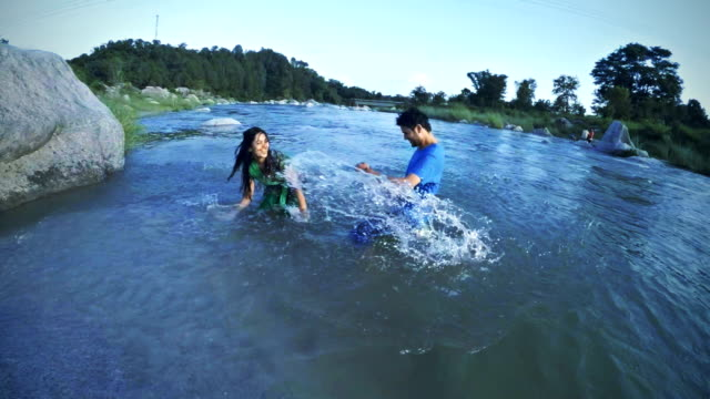 happy young couple doing fun in river. - crane shot stock videos & royalty-free footage