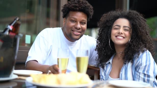 -肖像画のバーでビールを飲んで幸せな若いカップル - パルド人点の映像素材/bロール