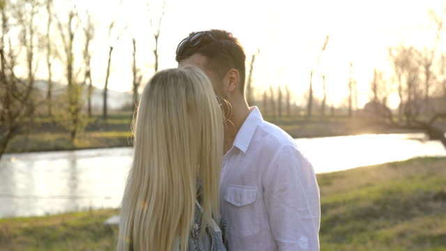 happy young couple embracing by the river - heterosexual couple stock videos & royalty-free footage