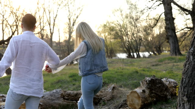 happy young couple embracing by the river - riverbank stock videos & royalty-free footage