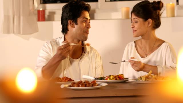 vídeos de stock, filmes e b-roll de ms happy young couple feeding each other while sitting in the restaurant / delhi, india - garfo
