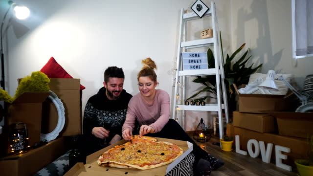 happy young couple have a pizza lunch break on the floor after moving into a new home with boxes around them - physical activity stock videos & royalty-free footage