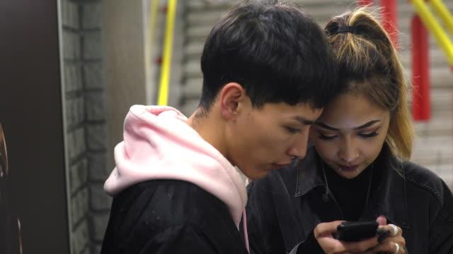 携帯電話で楽しんでいる幸せな若いカップル - 恋に落ちる点の映像素材/bロール