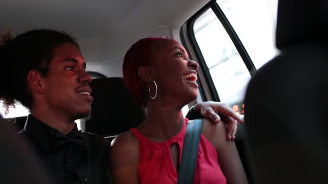 happy young couple in back of taxi as it drives through urban area at night. - hoop earring stock videos and b-roll footage