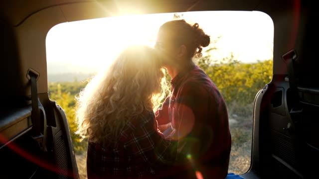 vidéos et rushes de heureux jeune couple dans le coffre de la voiture ouverte au coucher du soleil - insouciance