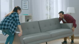 Happy Young Couple Moves New Couch into Living Room, Fall on it to Rest. Bright Modern Apartment with Stylish Furniture.