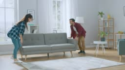 Happy Young Couple Moving New Couch into the Living Room, Fall on it to Rest. Bright Modern Apartment with Stylish Furniture.