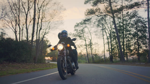 vídeos de stock, filmes e b-roll de slo mo. happy young couple on motorcycle drive down curvy forest road. - motocicleta