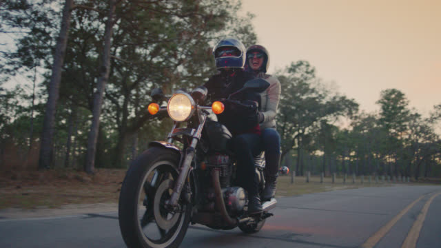 SLO MO. Happy young couple on motorcycle drive past on parkway drive.