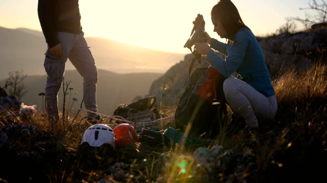 happy young couple packing their backpacks and climbing equipment for a hike in the alps - climbing equipment stock videos & royalty-free footage