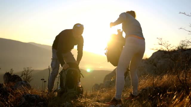 glückliches junges paar packt seine rucksäcke für eine wanderung in den alpen.wasserflasche - rucksack stock-videos und b-roll-filmmaterial