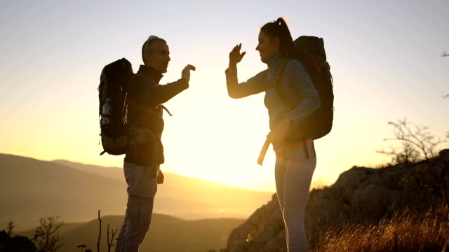 happy young couple packing their backpacks for a hike in the alps.water bottle - bag stock videos & royalty-free footage