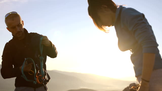happy young couple packing their climbing equipment and backpacks for a hike in the alps - climbing equipment stock videos & royalty-free footage