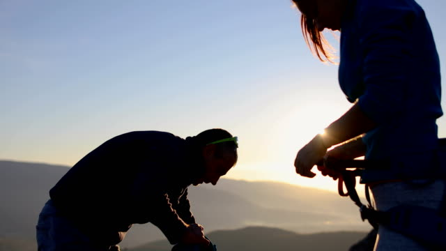 happy young couple packing their climbing equipment for a hike in the alps - climbing equipment stock videos & royalty-free footage