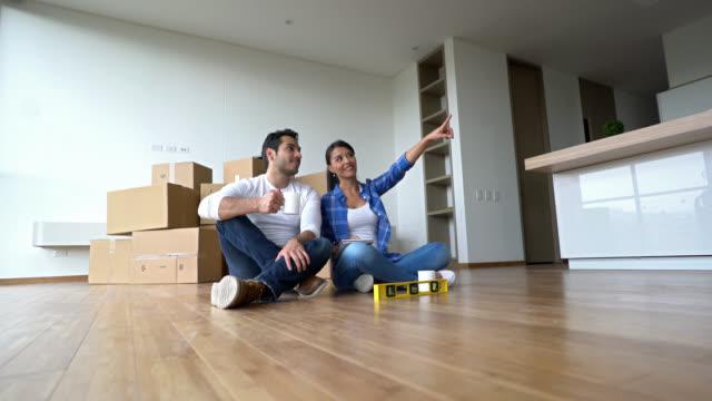 幸せな若いカップルが計画のインテリアにどのように彼らの新しいアパート - note pad点の映像素材/bロール