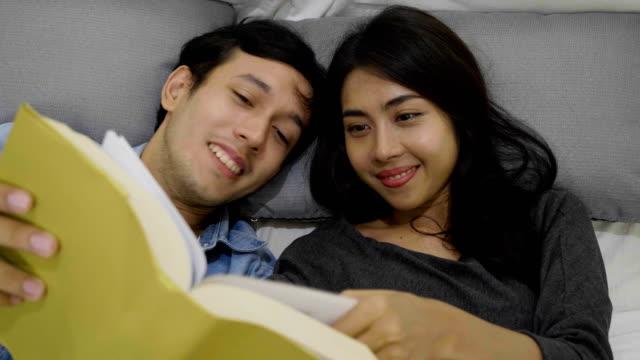 Glückliches junges Paar auf dem Bett liegend ein Buch lesen