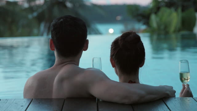 happy young couple relaxing in swimming pool,4k - bassängkant bildbanksvideor och videomaterial från bakom kulisserna