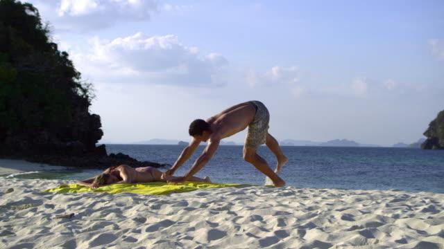 ws pan happy young couple relaxing on tropical beach, krabi, thailand - asciugamano video stock e b–roll